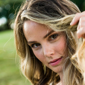 Close up view of woman peering into the camera lifting the front part of her hair as if she is playing peek a boo