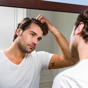Man running fingers through his hair while gazing in the mirror