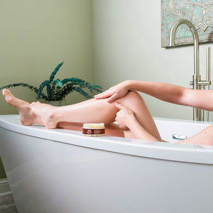 A woman rubbing Organic Eucalyptus Mint Sugar Body Scrub onto calf in the bathtub