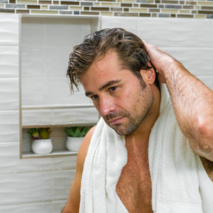 Man running fingers through his freshly washed hair