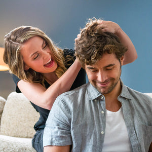 Woman happily running fingers through mans hair as he appears satisfied