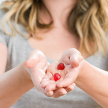 Load image into Gallery viewer, Woman holding bright red Nourish Biotin Gummies in hands