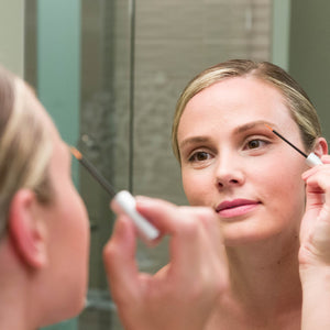 Woman applying Bang Brow Renewal Serum that includes Redensyl to her eyebrow in the mirror