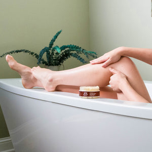 Woman rubbing Organic Coconut Sugar Body Scrub on her calf in the bathtub
