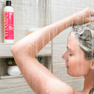 Woman Showering with vision of Vitamins Gold Label, Hair Growth Support Shampoo, with Biotin, Keratin, Saw Palmetto, Baicapil in the background