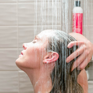 Woman showering with bottle of Vitamins Gold Label, Hair Growth Support Shampoo, with Biotin, Keratin, Saw Palmetto, Baicapil in the background