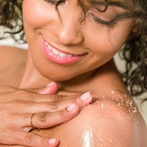 Woman rubbing Organic Eucalyptus Mint Sugar Body Scrub on her shoulder in the shower