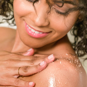 Woman rubbing Organic Coconut Sugar Body Scrub on her shoulder in the shower