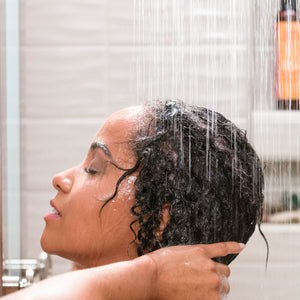 African American woman washing her hair in the shower