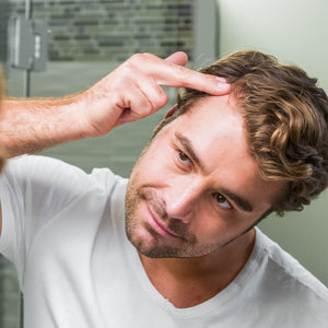 Man applying Nourish Burst Hair Growth Accelerating Serum to his widows peak