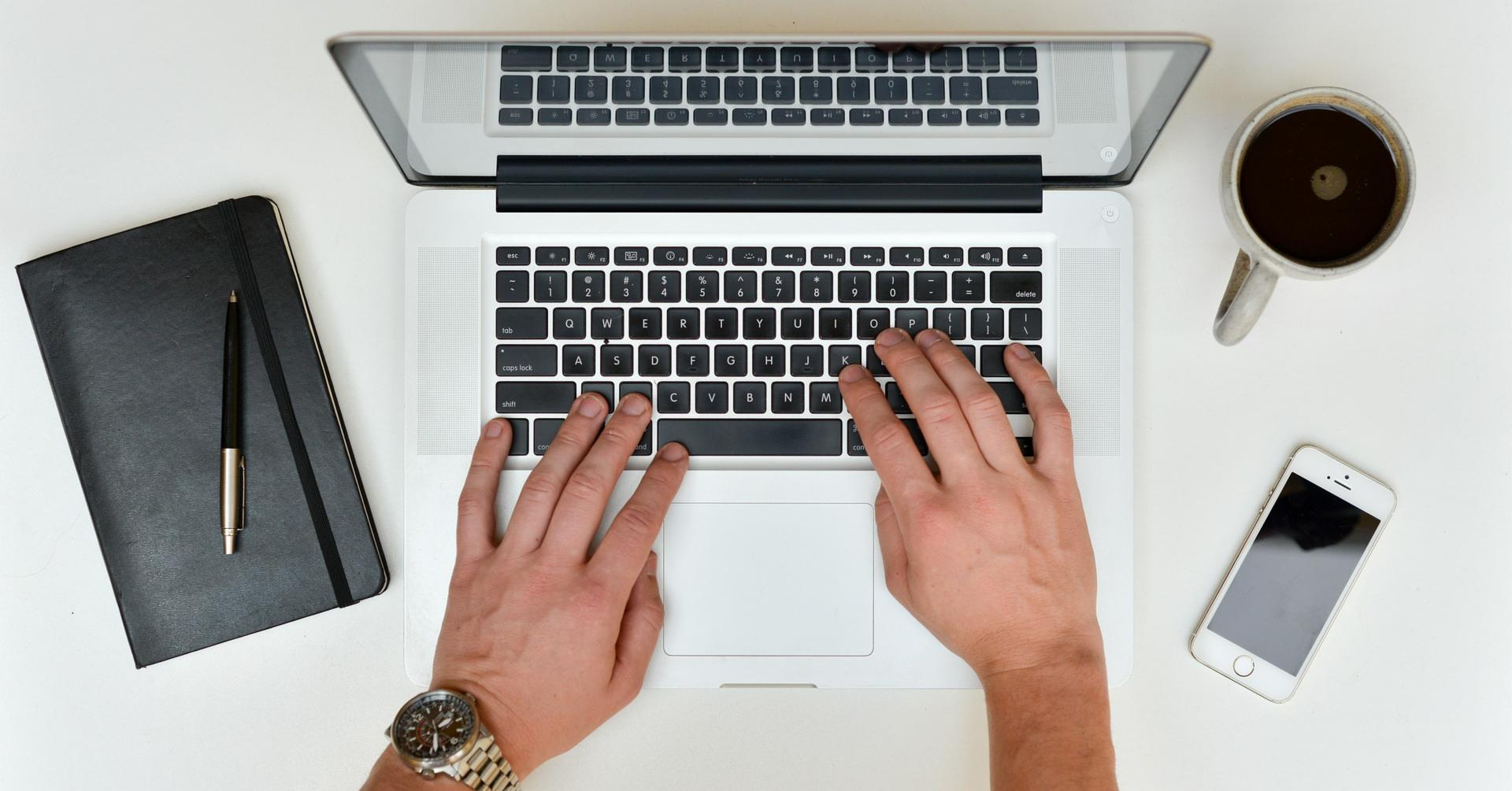 Hands writing a business proposal on a laptop