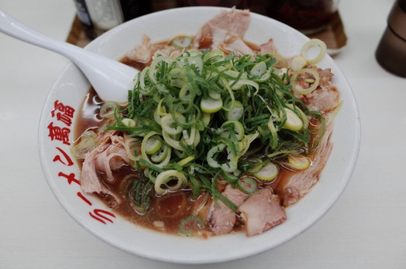 kyoto style donkotsu ramen topped with lots of roasted pork and scallions