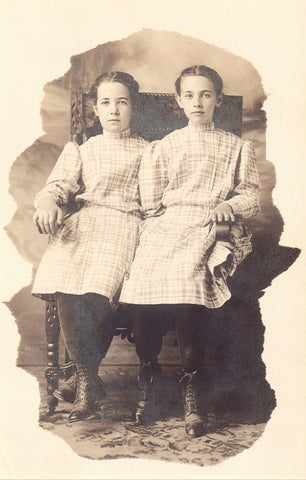 Real photo postcard front. 2 Girls Sitting in A Chair
