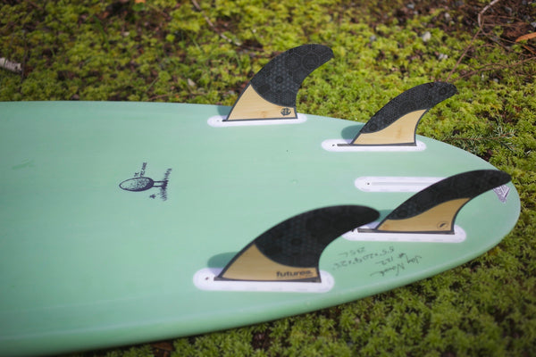 ecologyst sustainable free range eco-surfboard on grass with future fins quad
