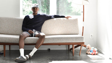 Man sitting wearing Grey Tencel Shorts and Navy Merino Sweater