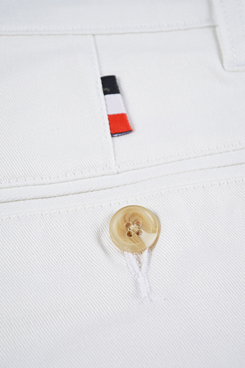 close up french flag tag and button on white chinos