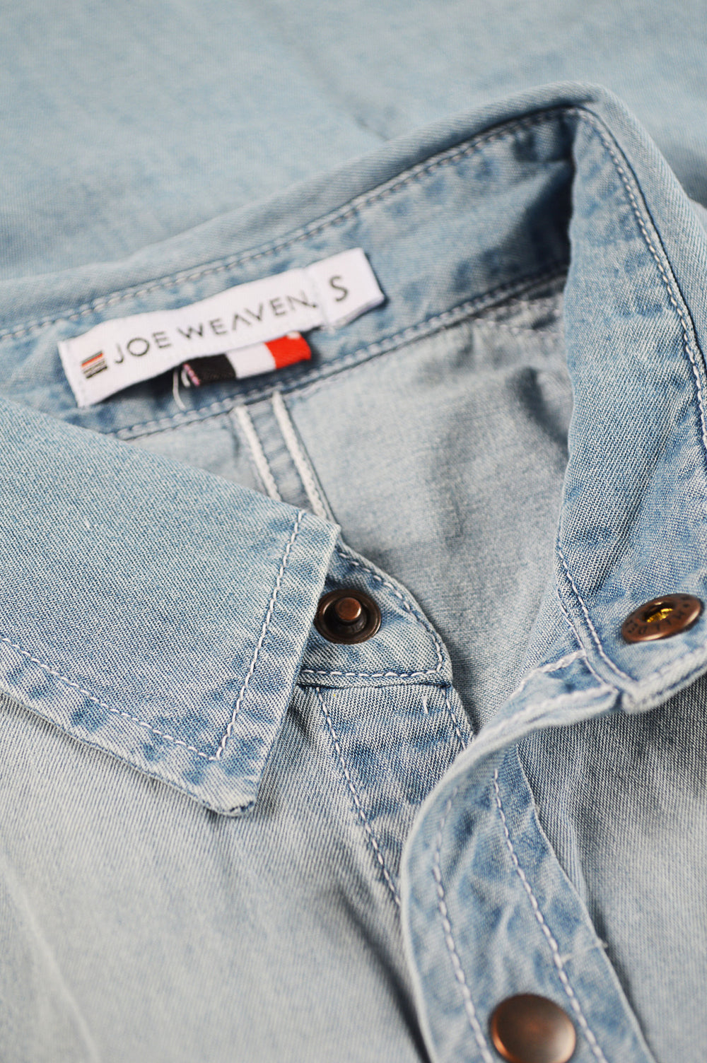 Close up front placket raw YKK snap buttons and logo tag