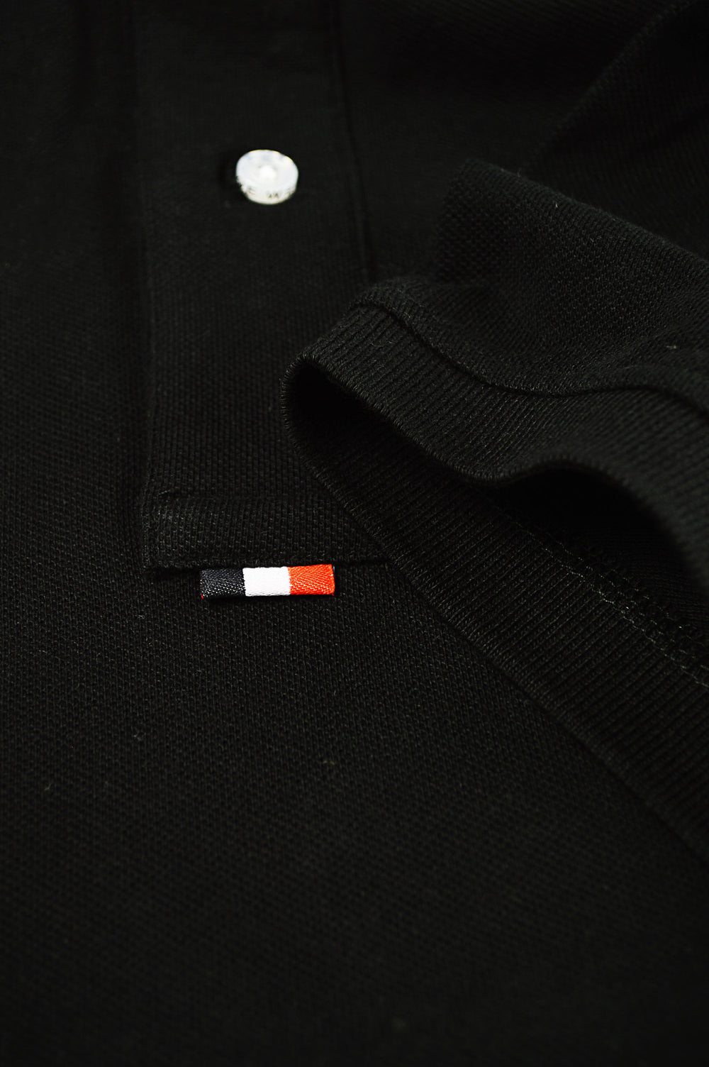 botton of placket black polo