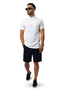 walking wearing white polo with french navy tailored shorts