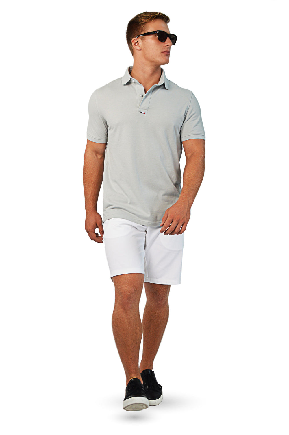 walking wearing grey tailored polo with white tailored shorts