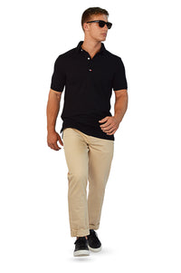 walking wearing black polo and tailored camel chinos
