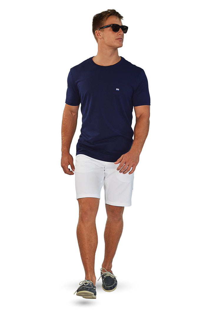 walking wearing navy t-shirt with white tailored shorts