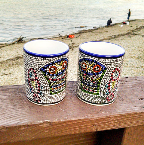 "longdesc=""2 Large Mosaic Glazed Ceramic Mugs that have two Red yellow Fishes and a blue and green basket containing round red and yellow pieces of bread loaves have been pattern pressed with a mosaic shape in black color. The almost square mosaic borders"