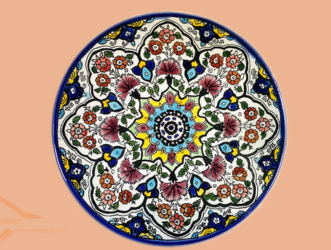Red yellow dark blue & light blue colorful teleidoscope patterns on glazed earthenware ceramic flat plates. Own&Adore Mystic Land Painted Creations. Eid Decorations. Palestinian pottery art and ceramic