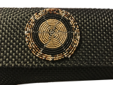 Detail of black canvas clutch with beaded decal