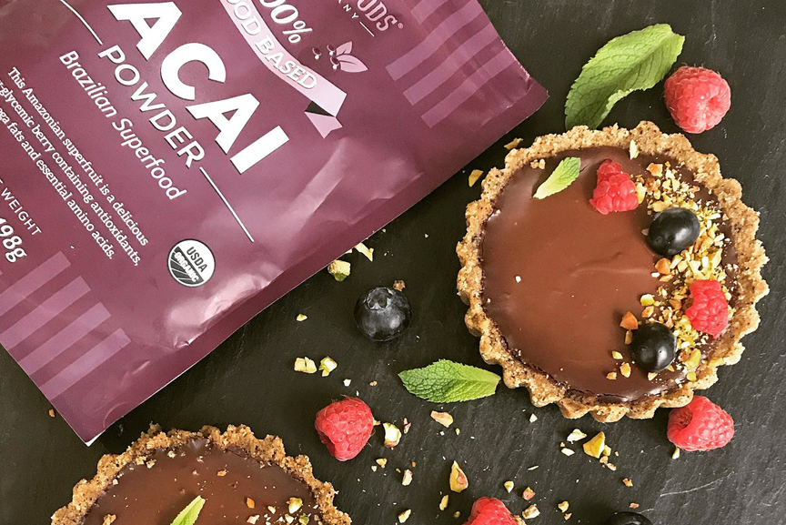 Two chocolate tarts with a bag of Acai