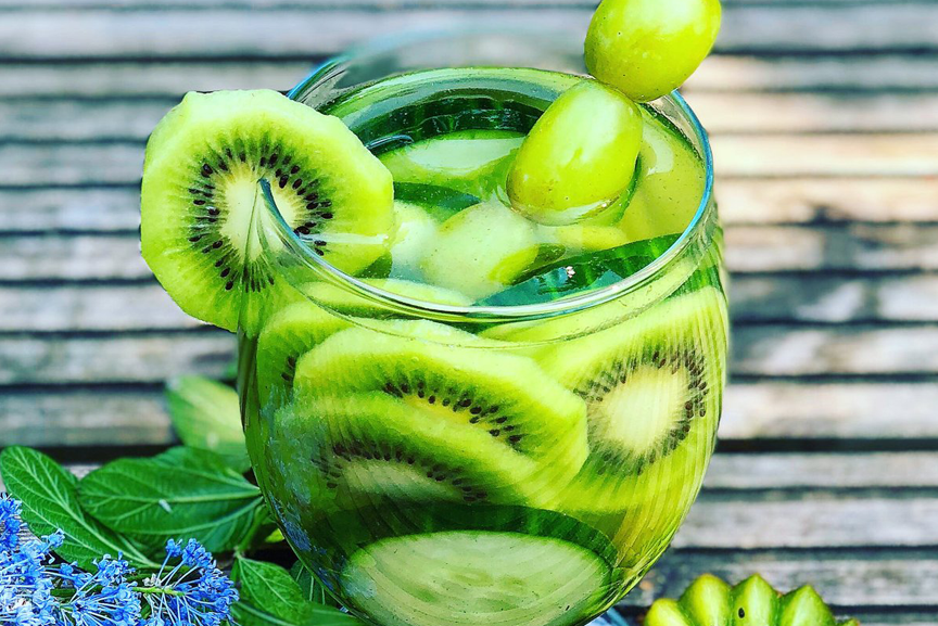 Glass of fruit water stuffed with kiwis and grapes.