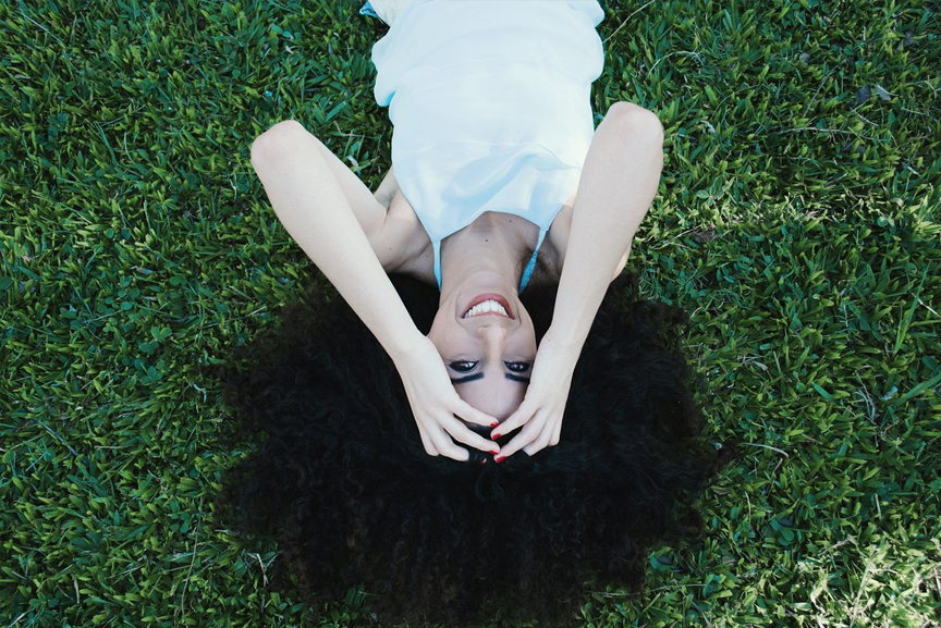 Woman laying on grass with her hair spread out