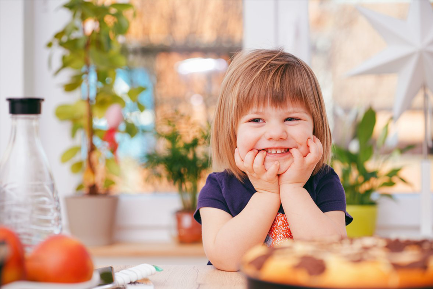 Child smiling and sitting in kitchen.