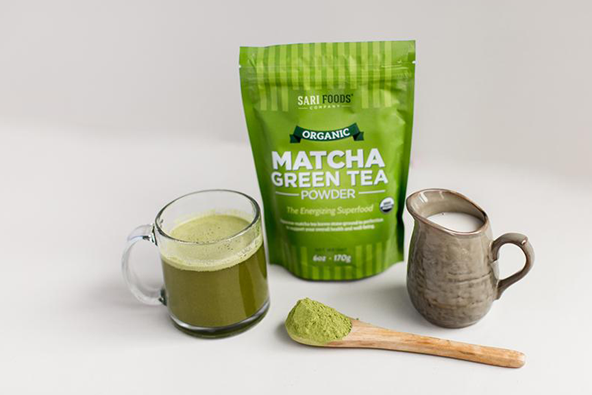 Matcha green tea latter in glass mug with milk pitcher