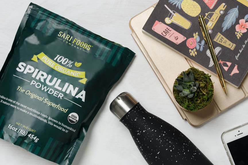 Spirulina package with water bottle and notebooks.