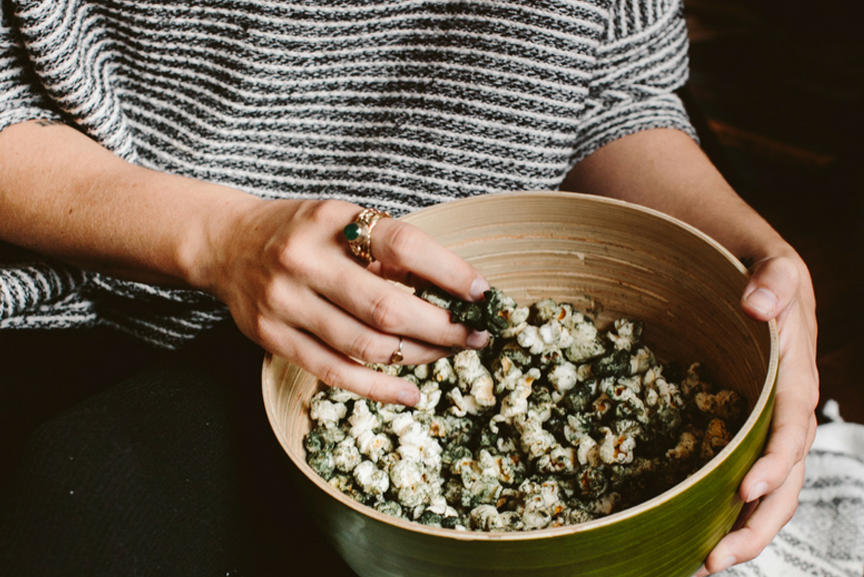 Woman holding bowl of Spirulina dusted popcorn
