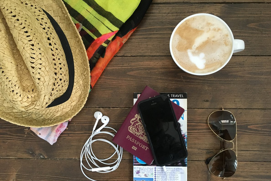 Travel items with a latte and a straw hat
