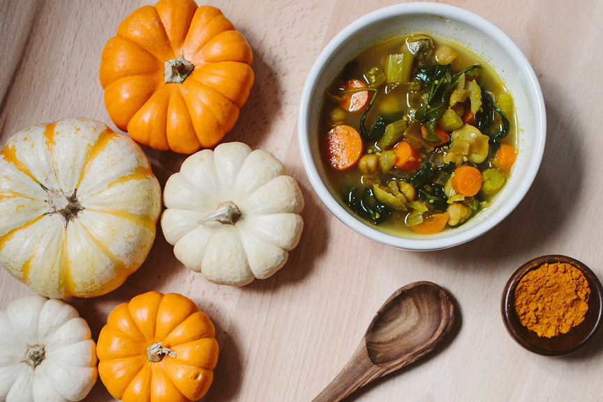 Warming turmeric soup in a bowl by pumpkin display