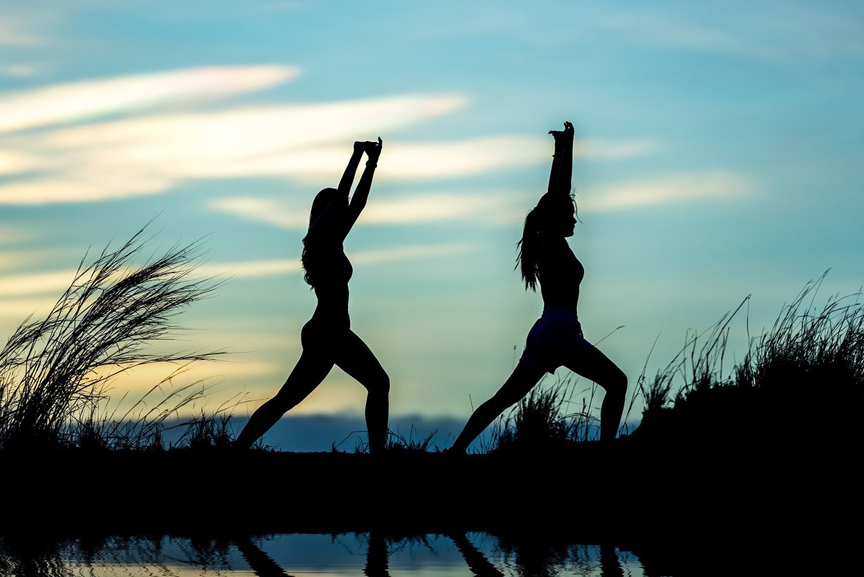 Two women doing yoga outdoors.
