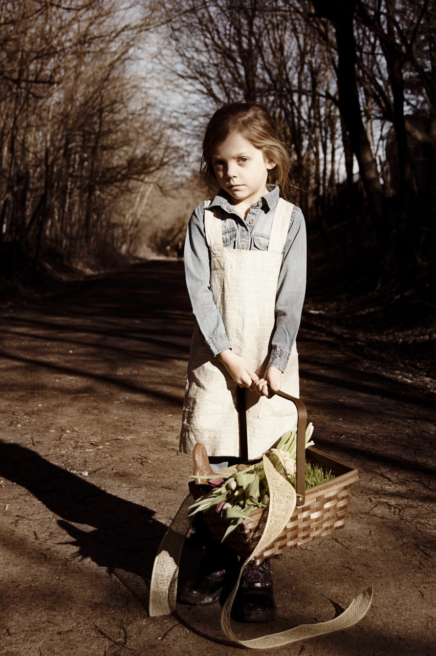 The child's pinafore is made from Smooth natural linen.