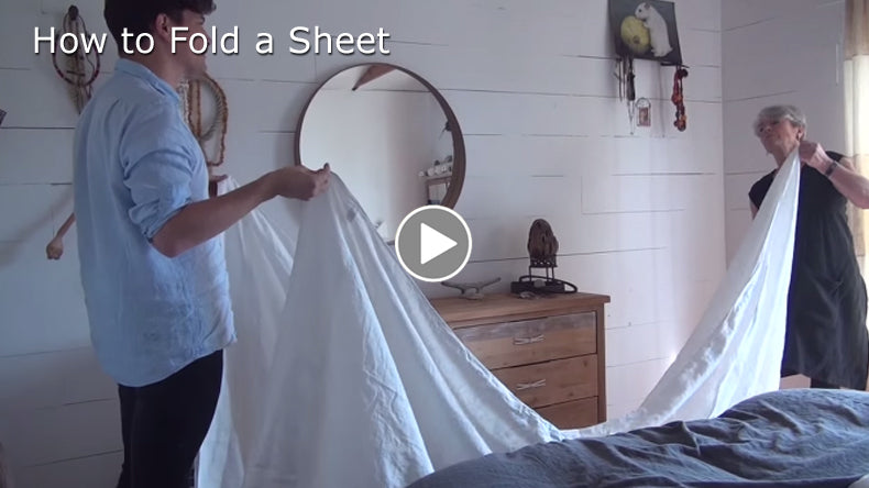 Tricia shows Felix how to fold a sheet