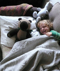 Child cuddling with toys under our natural and white linen blanket