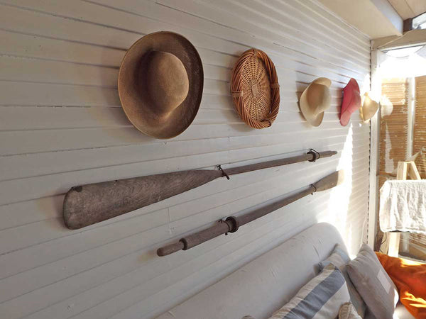 hats and oars hanging on an indoor-outdoor wall