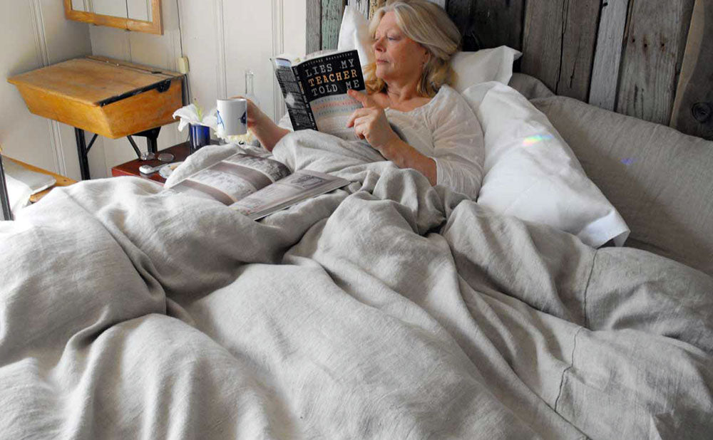 Tricia in bed with a Rough Linen Bed Makeover: linen duvet cover, linen sheet, linen pillow slips, linen shams, linen bolster.