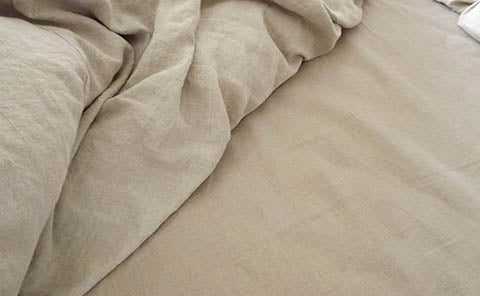 A Rough Linen Smooth natural sheet on the right, perfectly matches the color of the Orkney natural duvet cover