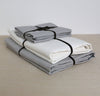 folded stack of 100% linen summer bed set including bottom sheet pillow cases summer cover blanket light grey pure white colors