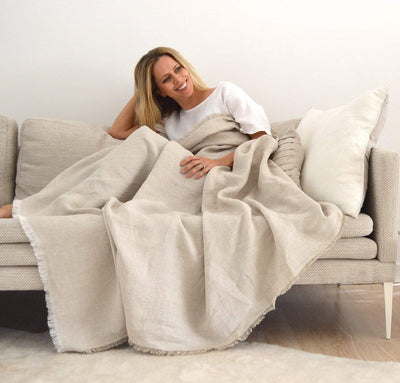woman wrapped in 100% linen lightweight soft fringe blanket throw two-toned natural light brown tan beige color