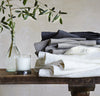 folded stack of 100% linen bath towels sturdy antimicrobial fast drying heavyweight Orkney linen fabric off-white white natural light brown tan charcoal black colors