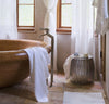 bathroom scene with 100% linen bathroom linens including bath sheet bath towel hand towel bath mat wash cloths heavyweight Orkney linen fabric off-white white color