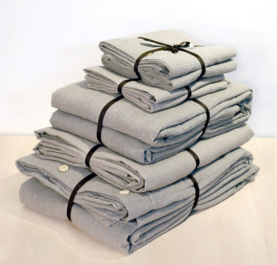 folded stack of 100% linen queen bed-in-a-bag set with duvet pillow shams summer cover flat sheets heavyweight Orkney linen fabric natural light brown beige tan colors